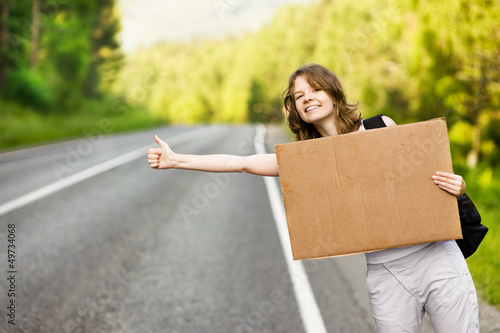 Pretty young woman tourist hitchhiking along a road