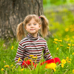 Lovely five-year girl sitting in grass