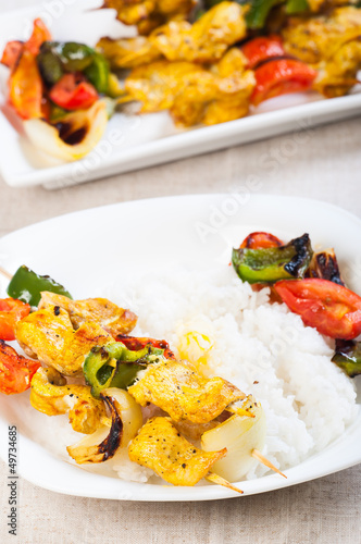 buttered rice topped with chicken kebab and vegetables on a side
