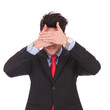 business man covers his eyes