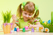 cute smiling child girl painting Easter eggs on green background
