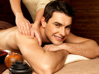 Smiling man having massage in the spa salon