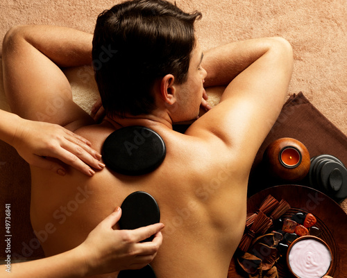man having stone massage in spa salon