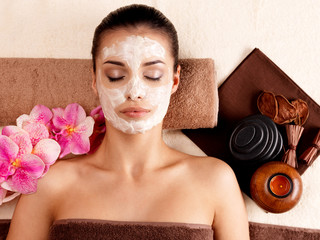 woman relaxing with cosmetic mask on face