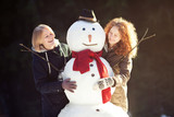 Two young women hugging snowman