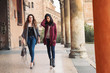 Two girls walking outdoors in Bologna, Italy.