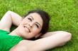 Attractive young girl laying on green grass.