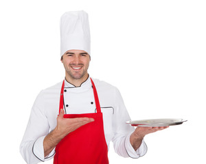 Portrait of cheerful chef presenting empty tray