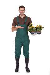 Happy young gardener holding flowers