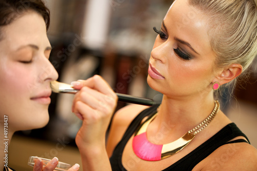 Attractive female make up artist at work.