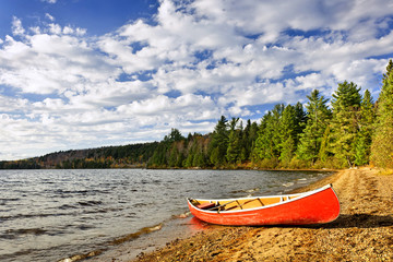 Red canoe on lake shore