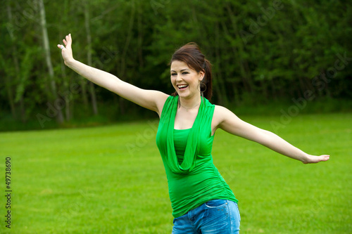 Cute girl with open arms in green field.