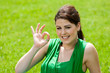 Girl in green field showing okay sign.