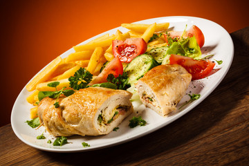 Fried wrapped meat, French fries and vegetables