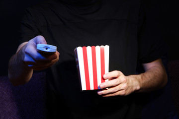 Man hand holding a TV remote control and popcorn,