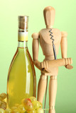 Mannequin with corkscrew and wine bottle, on green background