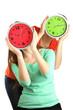 Girls holding clocks over face isolated on white