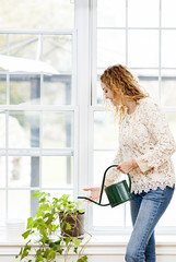 Smiling woman watering plant at home