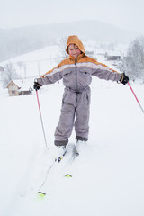 Little girl with skis in snowy mountain