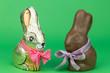zwei Schokoladenhasen mit Schleife auf grünem Hintergrund