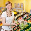 frau kauft grüne äpfel im supermarkt