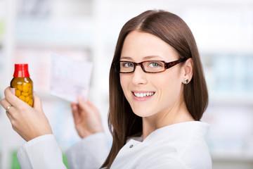 lächelnde apothekerin mit rezept und medikament