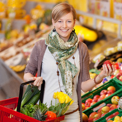 lächelnde frau kauft obst und gemüse
