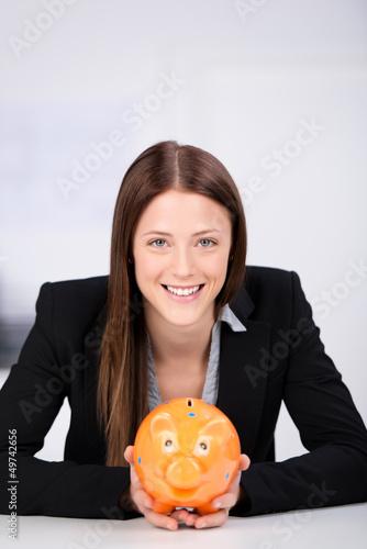 lächelnde frau hält sparschwein in der hand