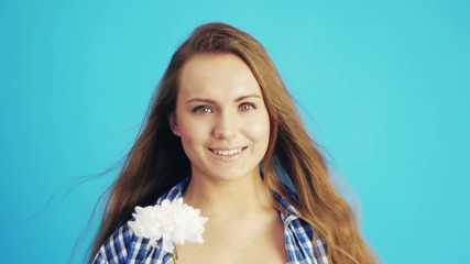 young woman sniffing white chrysanthemum on blue background