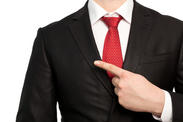 Isolated businessman in a suit points the finger at an object