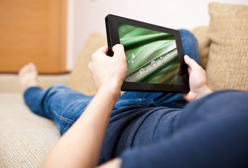 Man relaxing with tablet, laying on sofa