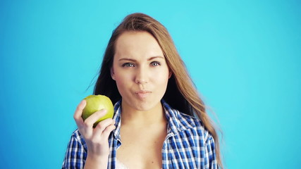 woman eating green apple and smiling
