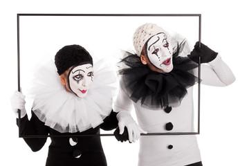 Zwei Clowns sehen durch einen Bilderrahmen nach unten