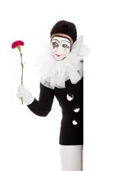 Weiblicher Clown mit Blume schaut ums Eck