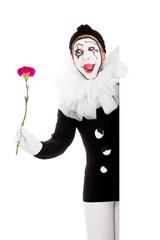 Weiblicher Clown mit Blume lachrt und schaut ums Eck