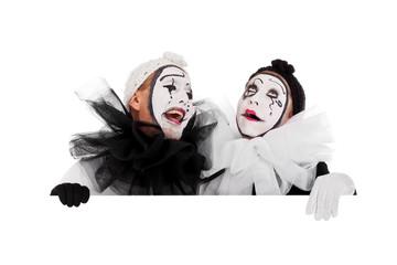 Zwei Clowns blicken lachend über eine Kante