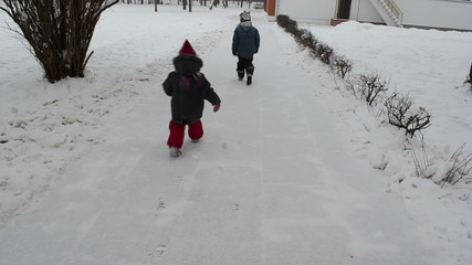 children go to nursery snow path and leave their footmark
