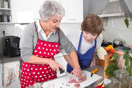 Junge lernt von der Oma kochen