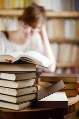 Frau vor Bücherstapel