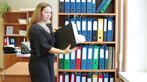 Young business woman coming to bookshelves to find file-folder