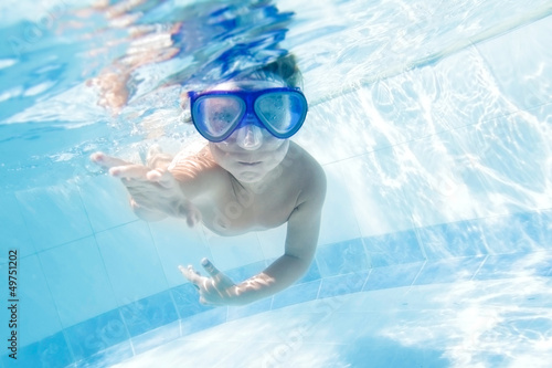 young child swimming underwater in pool
