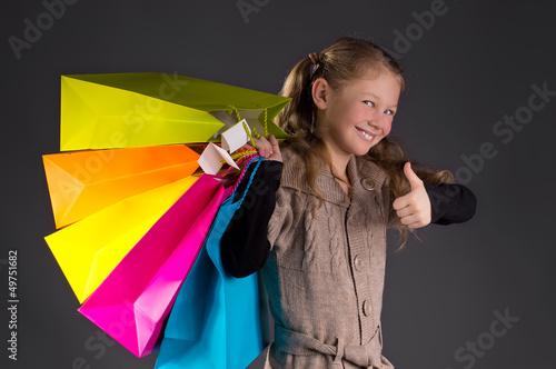 Fröhliches Mädchen mit Zöpfen und bunten Taschen