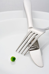 Fork, knife and a single green pea on a plate