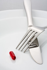 Fork, knife and a single red pill on a plate
