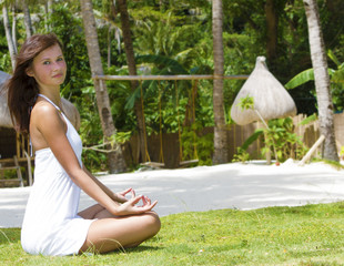 young woman meditating on natural background