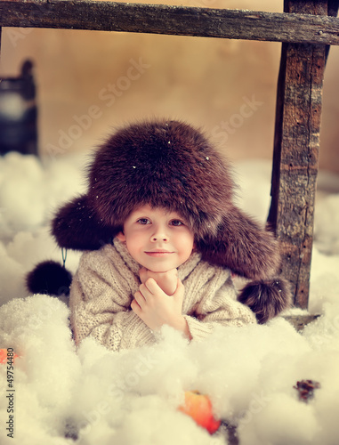 creative photo card is a smiling boy in a fur hat