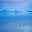Water surface in a blue morning, Italy. Hills on background