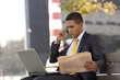 Businessman seated in a bench working