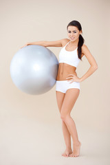 Fitness woman standing with gym ball