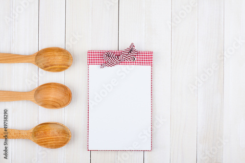 Recipe book, spoons on wooden background